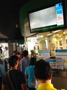 at a BTS station waiting in line to change bills into coins, to get into another queue for the ticket machine.